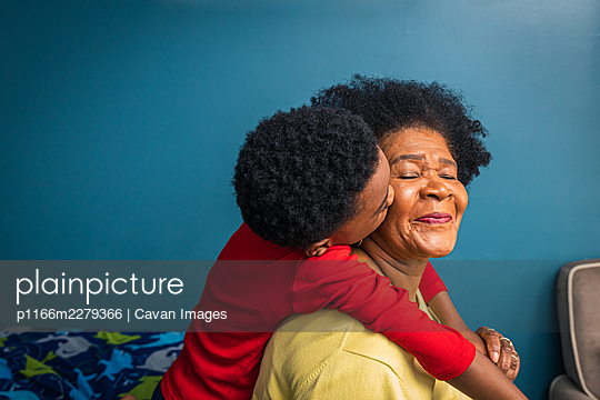 Grandson kissing grandmother on cheek by blue wall at home - p1166m2279366 by Cavan Images