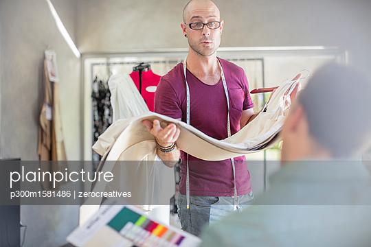 Fashion designer holding fabric in studio - p300m1581486 von zerocreatives