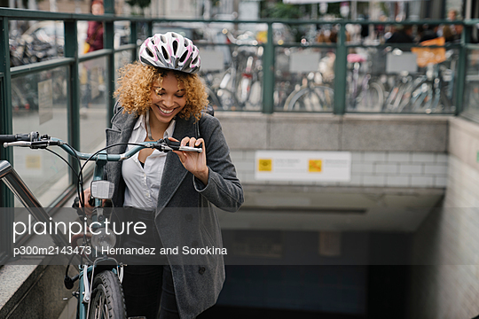 Happy woman with bicycle leaving subway station, Berlin, Germany - p300m2143473 by Hernandez and Sorokina