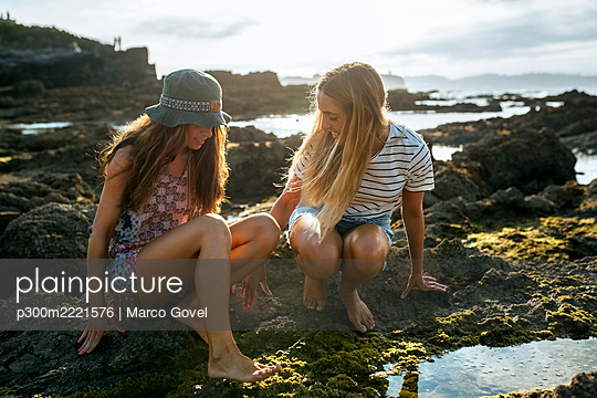 Young women crouching by puddle on rock at beach during sunny day - p300m2221576 by Marco Govel