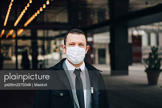 Portrait of businessman with protective face mask - p426m2270348 by Maskot