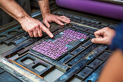 Cropped image of workers working on letterpress in workshop - p1166m1096221f by Cavan Images