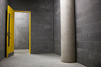 Grey Concrete Room With Open Bright Yellow Door  - p1291m1548110 by Marcus Bastel