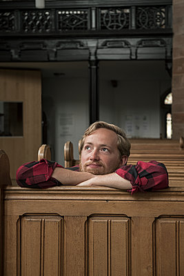 Young man sitting in a pew - p1437m2008195 by Achim Bunz