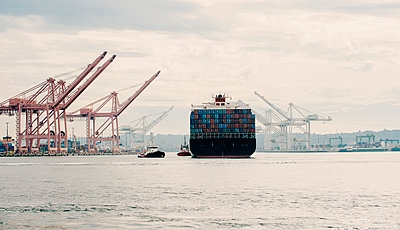 Tugboat and container ship in industrial harbor - p555m1414207 by Pete Saloutos