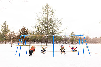Man and children swinging on row of playground swings in snow - p924m2074798 by Viara Mileva