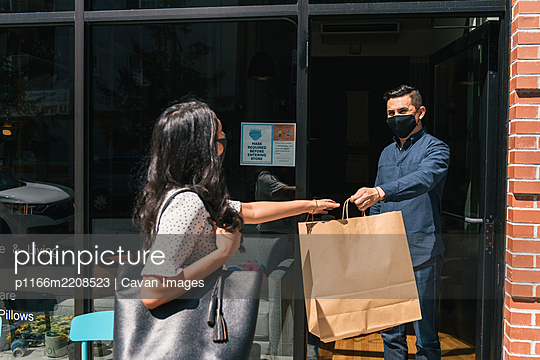 Picking up a purchase at local business while wearing mask - p1166m2208523 by Cavan Images
