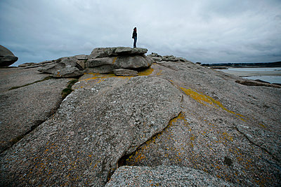 Woman on grey rocks looking at the sea, Tregastel, Brittany, France - p1028m2178724 by Jean Marmeisse
