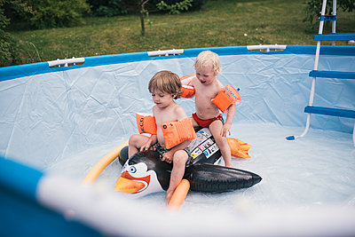 Two little boys playing in pool - p1046m1220963 by Moritz Küstner