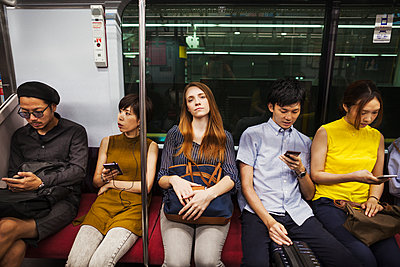 Five people sitting sidy by side on a subway train, Tokyo commuters.  - p1100m1531106 by Mint Images