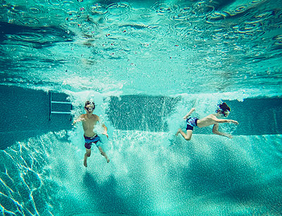 Underwater image of two boys jumping into a swimming pool together. - p1166m2138071 by Cavan Images