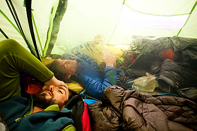 A climber rubs his head after a long day navigating through whiteout conditions while attempting to summit a mountain. Another climber sleeps in the vestibule of the tent trying to avoid the rain. - p1424m1501982 by Michael Hanson