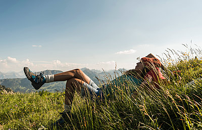 Austria, Tyrol, Tannheimer Tal, young woman lying on alpine meadow - p300m1188683 by Uwe Umstätter