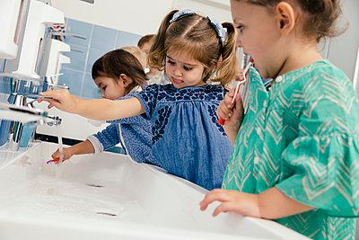 Children brushing their teeth in bathroom of a kindergarten - p300m1537489 by Mareen Fischinger