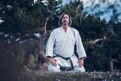 Senior man practicing karate outdoors, meditation - p300m2083877 von Oscar Carrascosa Martinez