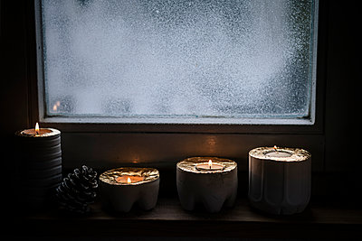 Four lighted advent candles and a fir cone in front of snow covered window - p300m885158f by Susan Brooks-Dammann