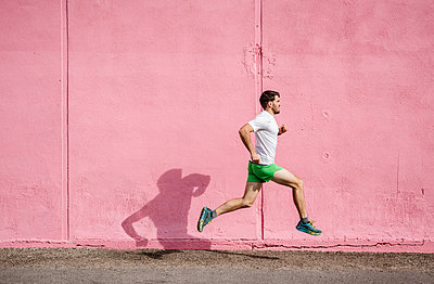 Young male runner running past pink wall - p924m2074493 by JFCreatives