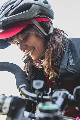 Woman on her bike, wearing helmet, smiling - p924m2252491 by Alex Eggermont