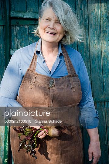 Senior woman harvesting beetroot, garden apron made of old linen pants - p300m2103518 von Gianna Schade