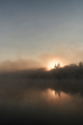 Germany, Dark lake in the back light with fog - p1312m2278431 by Axel Killian