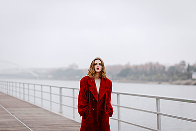 Portrait of young woman wearing red coat on a bridge during rainy day - p300m2160689 von Tania Cervián