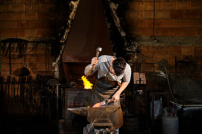 Male metal worker forging metal with hammer at blacksmith shop - p300m2281444 by Antonio Ovejero Diaz