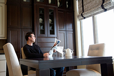 Man reading the newspaper at home - p4428139f by Design Pics