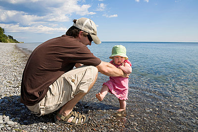 Dad Holding His Baby Daughter As She Hesitates To Wade In The Water Of Lake Ontario - p442m883744 by Mary Ellen McQuay