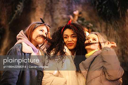 Female friends being silly making funny faces with hair mustaches - p1166m2258314 by Cavan Images