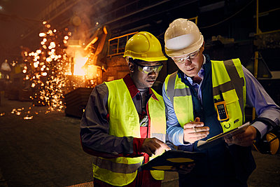 Steelworkers using digital tablets in steel mill - p1023m1519929 by Agnieszka Olek