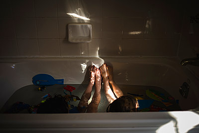 High angle view of siblings playing in bathtub - p1166m1533770 by Cavan Images