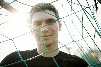Portrait of smiling young man behind football net - p300m1028747f by Gabi Dilly