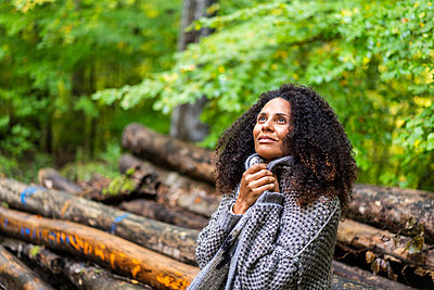 Thoughtful woman looking up while sitting in forest - p300m2250246 by Annika List