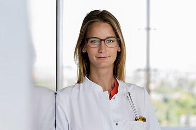 Smiling female doctor wearing eyeglasses leaning on wall in hospital - p300m2281508 by Buero Monaco