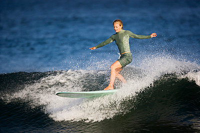 A female surfer riding a longboard at Surfrider Point in Malibu, California - p3437640f by Ty Milford