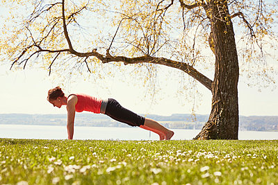 Side view of woman doing yoga push up - p429m1156071 by Stephen Lux