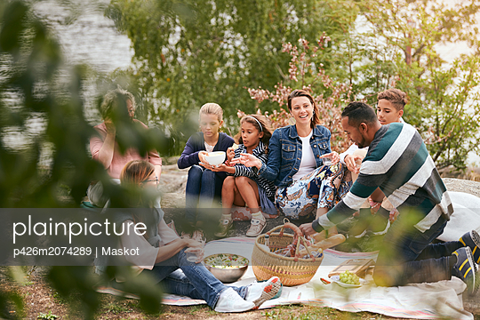 Happy family and friends having food on lakeshore in park - p426m2074289 by Maskot