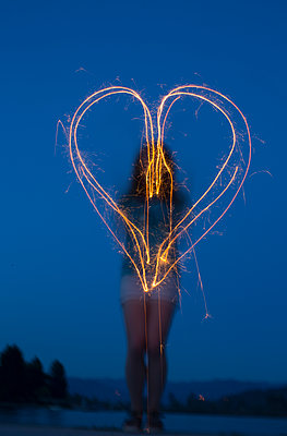 Woman making a heart while light painting with a sparkler - p1166m2088457 by Cavan Images