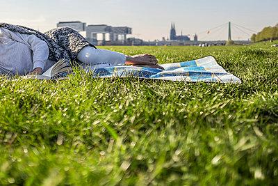 Woman reading book on blanket in meadow - p300m1023068f by Richárd Bellevue
