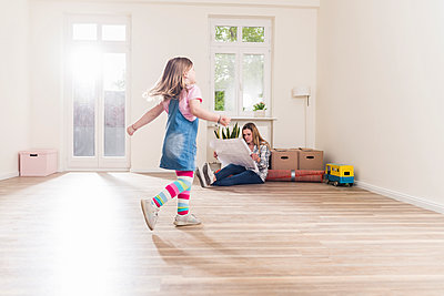 Happy girl running in empty apartment with mother reading plan - p300m1459825 by Uwe Umstätter