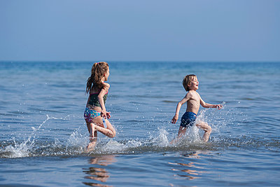 boy and girl playing at seashore - p300m884870 by Andreas Pacek