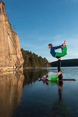 Couple doing yoga on frozen lake - p312m1472002 by Fredrik Schlyter