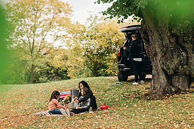 Parents with daughters enjoying picnic during autumn - p426m2195259 by Maskot