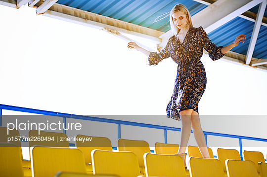 Young adult blond woman having fun at the empty stadium with yellow seats - p1577m2260494 by zhenikeyev