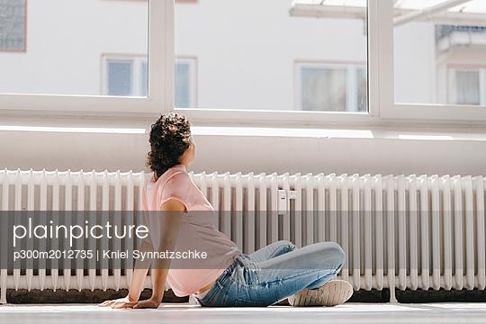 Woman sitting on ground, looking out of window - p300m2012735 von Kniel Synnatzschke