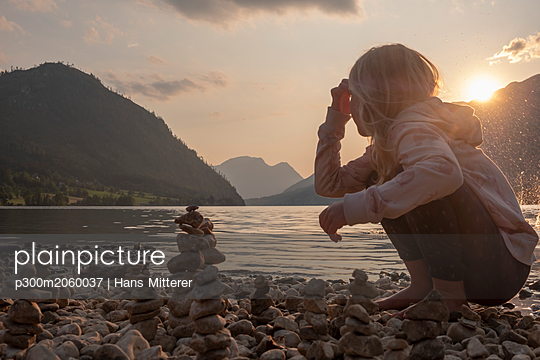 Austria, Ausseer Land, Girl building cairns at lakeshore - p300m2060037 by Hans Mitterer