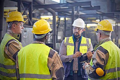 Supervisor talking with steelworkers in steel mill - p1023m1519928 by Agnieszka Olek