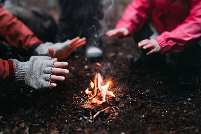 Cropped image of mother and daughter warming hands at campfire - p1166m1474549 by Cavan Images