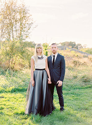 Sweden, Groom and bride standing together holding hands - p352m1141924 by Isabelle Hesselberg