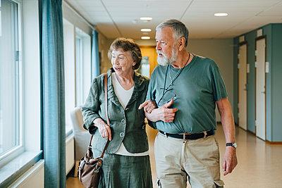 Senior couple walking arm in arm at elderly nursing home - p426m2149318 by Maskot